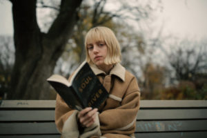 woman on park bench reading book